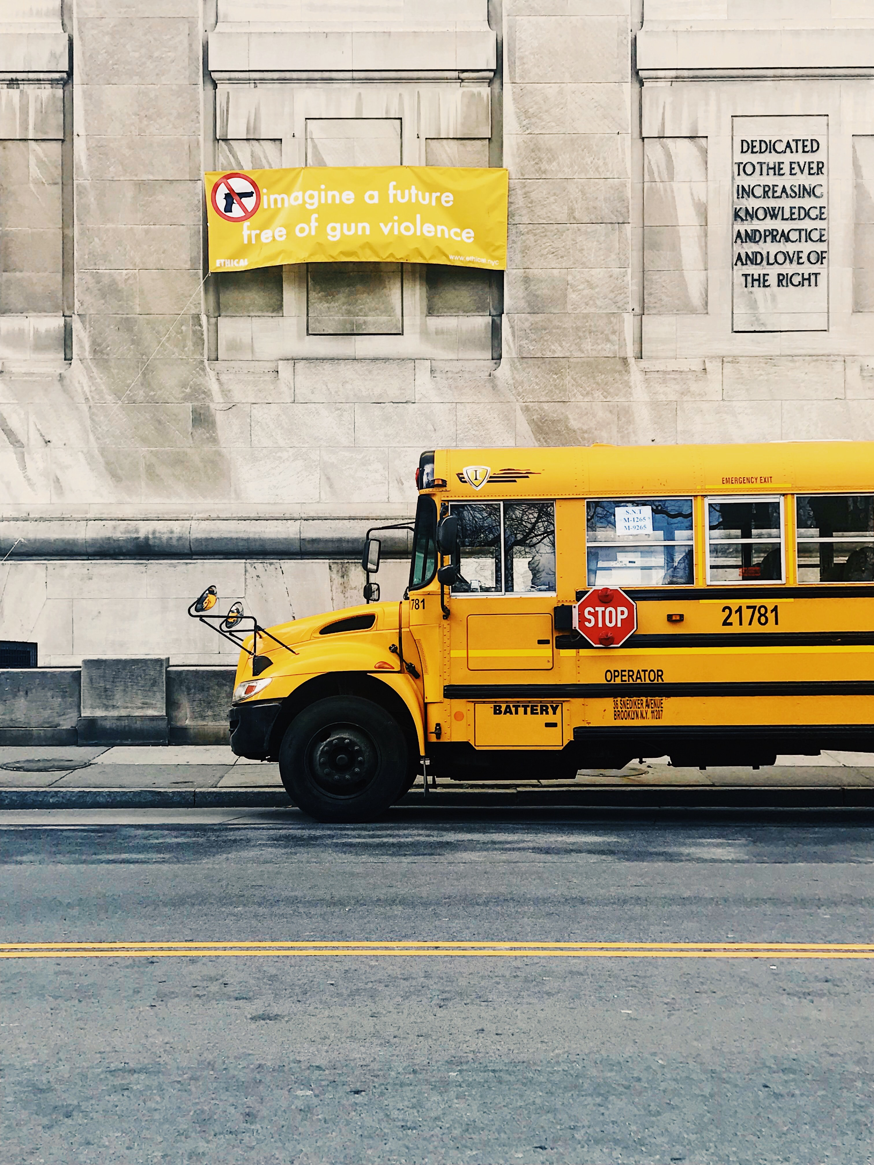 school bus in front of an anti-gun poster