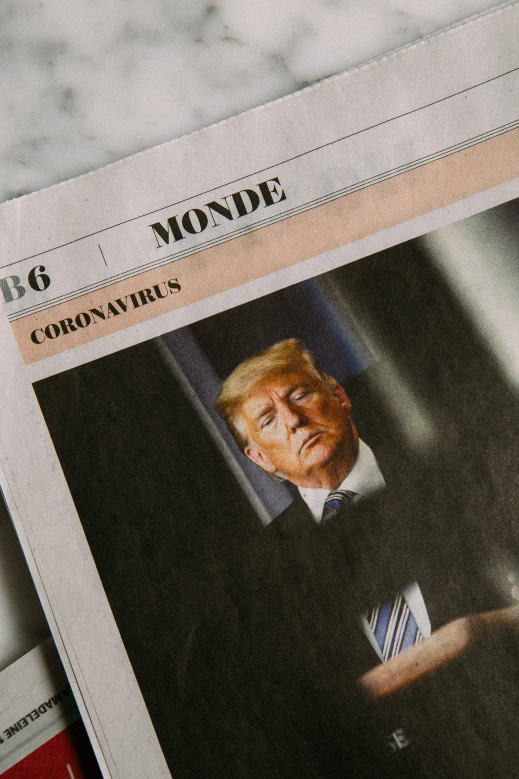 "A newspaper features an image of Trump looking somber under the word ""coronavirus."""