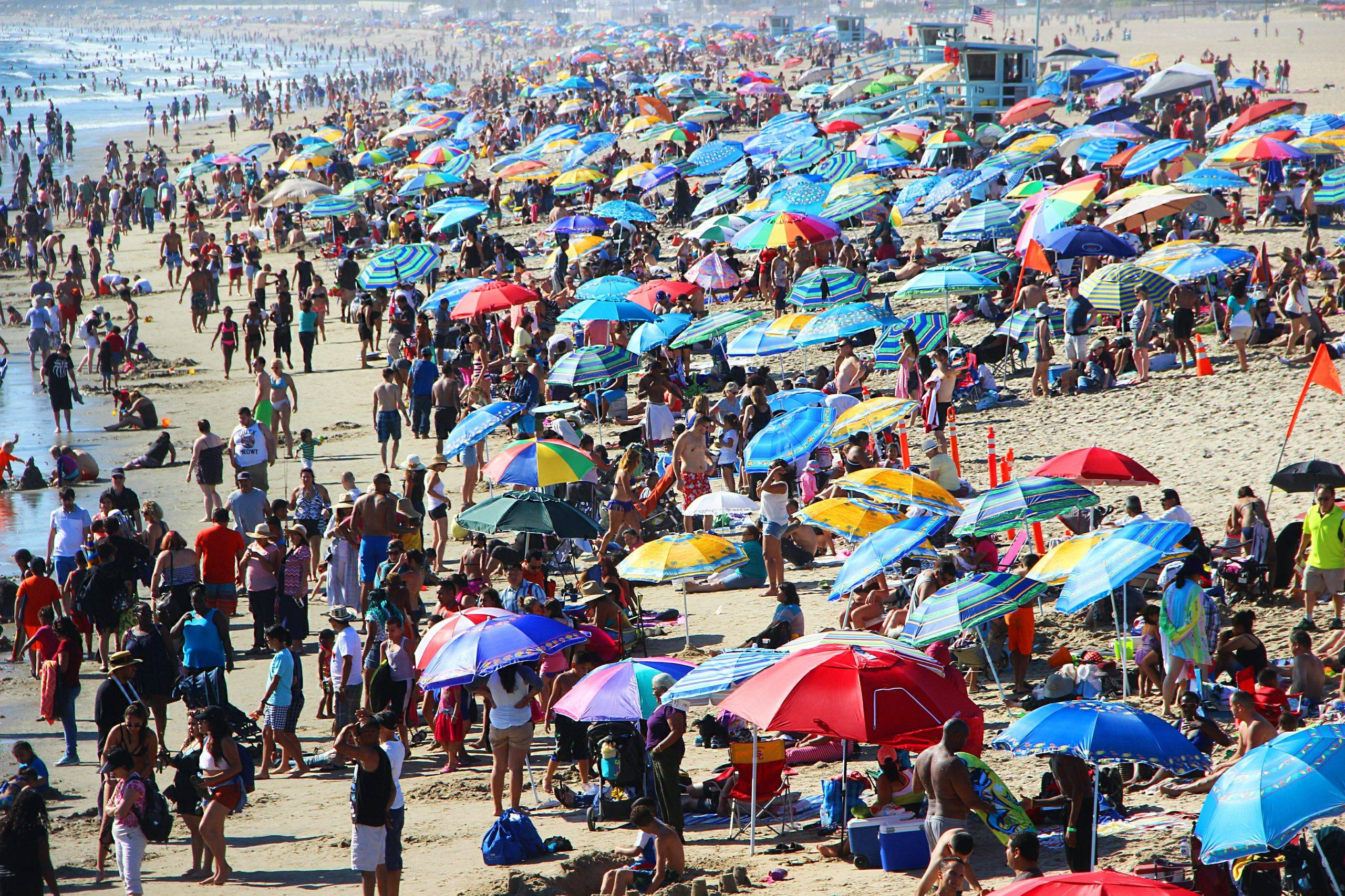 A crowd congregates on the beach on a sunny day.